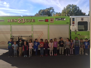 "Firemen came to visit first grade to teach them about fire safety during ""Fire Safety Week."" The students got to see the inside of a fire truck and ambulance and learn about some of the important tools that they use."
