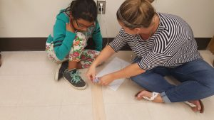 teacher helping with hot glueing